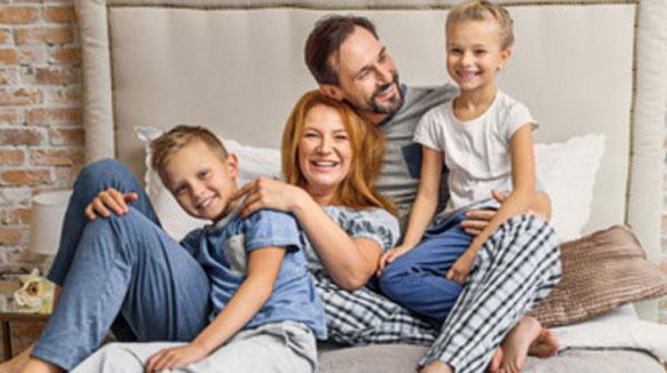 Папа, мама, дочка и сын на кровати. Веселые