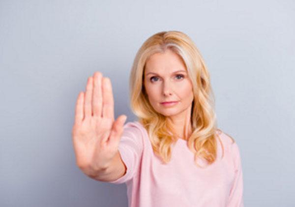 Женщина средних лет выставляет перед собой руку, указывая на протест