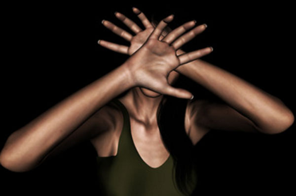 Женщина прячет свое лицо руками. Она в панике