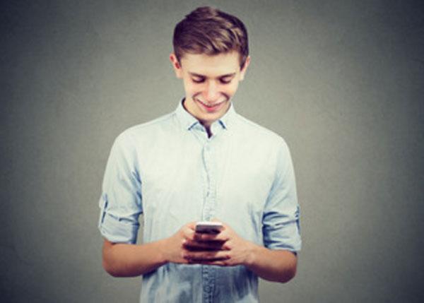Парень пишет сообщение на смартфоне и улыбается