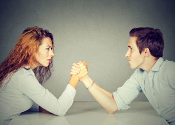 Мужчина а женщина борется на руках