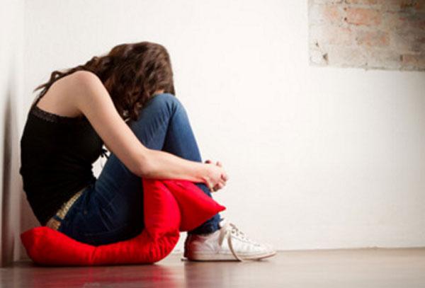 Девочка сидит на полу на подушке. Она прижала голову к коленкам