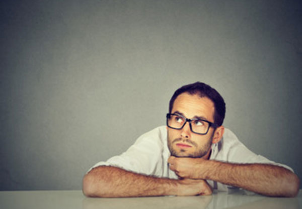 Парень в очках сидит в задумчивости