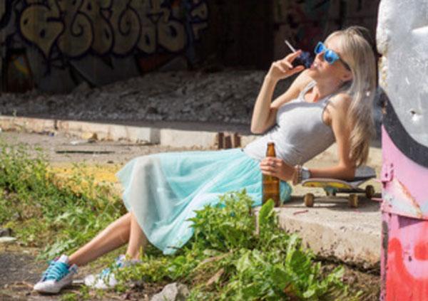 Девушка курит и пьет, облокотившись на бордюр